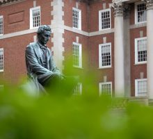 A statue of Abraham Lincoln is obscured slightly by blurred out foliage in the foreground with Maxwell College in the background.