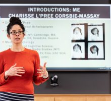 Faculty member Charisse L'Pree stands facing class with powerpoint presentation in the background. Click to see Curriculum Proposal Deadlines.