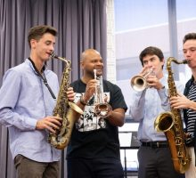 Four men play brass instruments together. Click to learn more about honorary degrees.